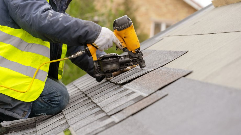 Workman using pneumatic nail gun install tile on roof of a house